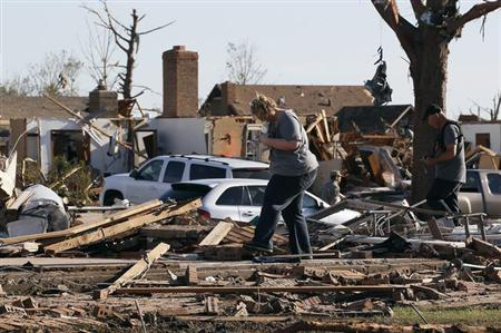 A couple tries to find valuables in their tornado-destroyed home in Moore, Oklahoma May 21, 2013. REUTERS/Rick Wilking