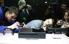 Сотрудники СМИ фотографируют Xbox One на пресс-конференции в Редмонде, штат Вашингтон 21 мая 2013 года. Microsoft Corp представил новый Xbox One, первую игровую консоль за последние восемь лет, призванную прижать конкурентов на сложном рынке. REUTERS/Nick Adams