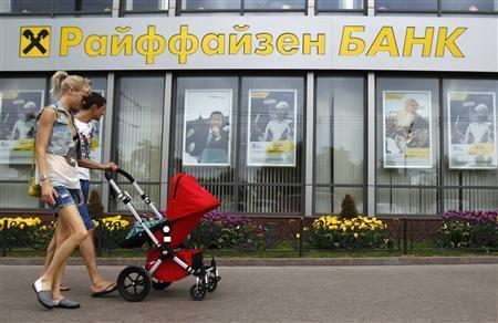 Pedestrians walk past a Raiffeisen Bank branch in Moscow May 19, 2013. REUTERS/Sergei Karpukhin