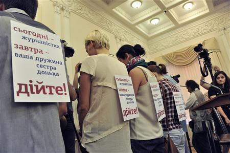 Journalists show off signs, pinned to their backs, as they stage a silent protest during a cabinet meeting in Kiev, May 22, 2013. REUTERS/Stringer
