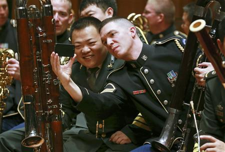 Musicians from the military bands of China's People's Liberation Army and the U.S. Army take photos during a rehearsal for their joint concert at the National Centre for the Performing Arts in Beijing, in this October 29, 2012 file photo. REUTERS/China Daily/Files