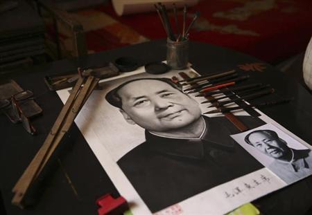 A photo of former China's Chairman Mao Zedong is placed on top of a Mao charcoal portrait that was painted by Chinese farmer Yang Chuanye, in Jishan county, Shanxi province, May 13, 2013. REUTERS/Stringer