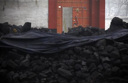 A man stands in front of a house that is surrounded by piles of coal near the town of Dangcheng in Quyang county, located 250 km (155 miles) southwest of Beijing December 7, 2011. REUTERS/David Gray