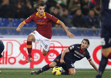 AS Roma's Erik Lamela (L) is challenged by Cagliari's Daniele Conti during their Italian Serie A soccer match at the Olympic stadium in Rome February 1, 2013. REUTERS/Tony Gentile