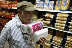 Мужчина несет туалетную бумагу в супермаркете в Каракасе 17 мая 2013 года. Покупатели за считанные минуты разбирают пачки с туалетной бумагой в торговых залах венесуэльских супермаркетов под напоминания из громкоговорителей о том, что каждый может взять не более четырех упаковок. REUTERS/Jorge Silva