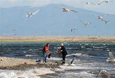 Женщины собирают рыбу в Охотском море около городка Ола на Чукотке, 20 июля 2009 года. Землетрясение магнитудой 8,2 балла произошло в Охотском море у побережья Камчатки, сообщила Геологическая служба США. Отголоски землетрясения ощущались в пятницу утром в Москве. REUTERS/Robin Paxton
