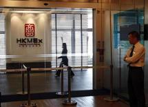 A security guard stands at the entrance as an office worker walks inside the Hong Kong Mercantile Exchange in Hong Kong May 23, 2013. REUTERS/Bobby Yip