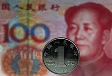 Монета в один юань на фоне банкноты в 100 юаней в Пекине, 11 мая 2013 года. Китай в этом году продолжит делать процентные ставки более либеральными, а юань - более отзывчивым к действию рыночных сил и более конвертируемым, заявило правительство в пятницу. REUTERS/Petar Kujundzic