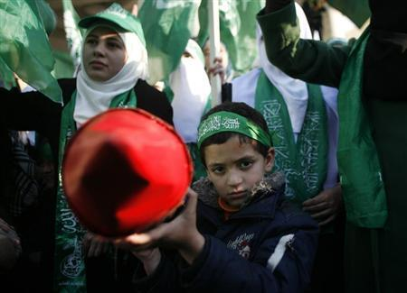 A Palestinian boy poses as he holds a model of rocket during a rally in the West Bank city of Nablus, marking the 25th anniversary of the founding of Hamas December 13, 2012. REUTERS/Muammar Awad