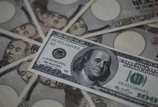 Купюра в 100 долларов США на банкнотах номиналом 10.000 иен в Токио 28 февраля 2013 года. Доллар снижается к иене, так как резкое падение японских акций побудило инвесторов перевести средства с валютного рынка на рынок облигаций. REUTERS/Shohei Miyano