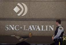 A Royal Canadian Mounted Police (RCMP) officer looks at a receptionist at the headquarters of SNC Lavalin in Montreal April 13, 2012. REUTERS/Christinne Muschi