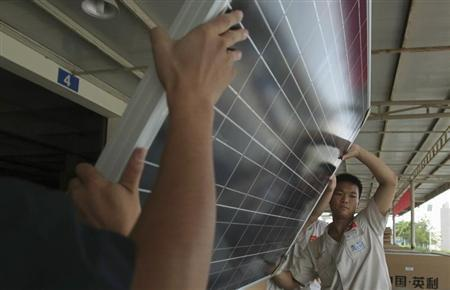 Employees examine newly-made solar panels before boxing for shipment at a factory of Yingli Solar in Baoding, Hebei province August 2, 2012. REUTERS/Pillar Lee