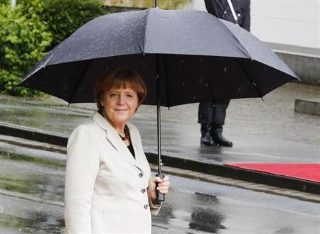 German Chancellor Angela Merkel stands under an umbrella as she waits for the arrival of Netherlands' Prime Minister Mark Rutte before their bilateral talks in the western German town of Kleve May 23, 2013. REUTERS/Wolfgang Rattay