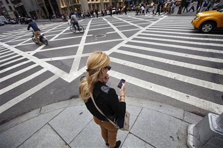 A woman uses her Apple iPhone while waiting to cross 5th Avenue in New York, September 20, 2012. REUTERS/Lucas Jackson
