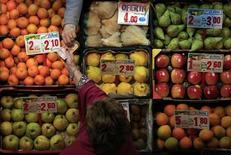 Женщина берет деньги у продавца на рынке в Севилье 28 ноября 2012 года. Погруженная в рецессию еврозона в этом году еще сильнее отстанет от США и Японии, где ситуация в целом улучшается, сообщила Организация экономического сотрудничества и развития (ОЭСР), сократив прогноз роста мировой экономики. REUTERS/Marcelo del Pozo