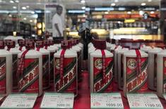 A customer walks past a glass case displaying Maotai liquors, a form of baijiu, with different price tags at a supermarket in Shenyang, Liaoning province, in this August 8, 2012 file photo. Chinese baijiu, a flammable, pungent white liquor averaging a 110-proof wallop, is the world's most consumed form of liquor thanks to its popularity in China, but for the first time distillers are looking to develop export markets.REUTERS/Stringer/Files