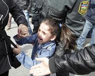 """Азербайджанская полиция конвоирует девочку, выкрикнувшую """"Свобода!"""" на акции протеста в Баку 17 апреля 2011 года. Оппозиция зовёт надеется убедить лауреата """"Оскара"""" баллотироваться в президенты Азербайджана на выборах в октябре. REUTERS/Irada Humbatova"""