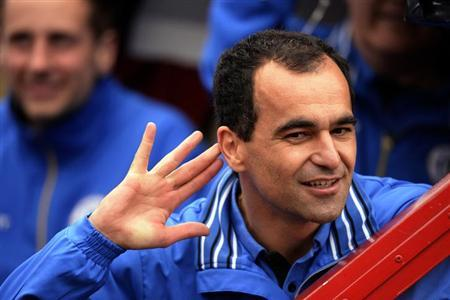 Wigan Athletic's manager Roberto Martinez holds his hand to his ear as the crowd cheers during a victory parade after the team won the English FA Cup in Wigan, northern England May 20, 2013. REUTERS/Nigel Roddis
