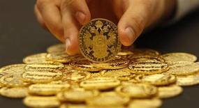Работник австрийского аукционного дома Dorotheum держит золотую монету в Вене 16 апреля 2013 года. Цены на золото поднялись до недельного максимума благодаря спаду на азиатском фондовом рынке, но драгметалл по-прежнему рискует потерять привлекательность как надежный актив на фоне опасений сокращения стимулирующих программ ФРС. REUTERS/Leonhard Foeger