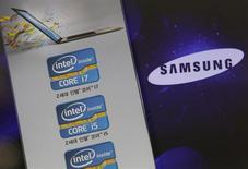 Логотип Samsung Electronics на фоне рекламы процессоров Intel в магазине в Сеуле 21 июня 2012 года. Samsung Electronics выбрала процессор Intel Corp для новой версии своих планшетных компьютеров на ОС Android, сообщил Рейтер источник, близкий к планам компании. REUTERS/Choi Dae-woong
