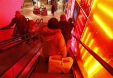 A woman goes down an escalator at a Toys R Us store in New York, December 14, 2010. REUTERS/Shannon Stapleton