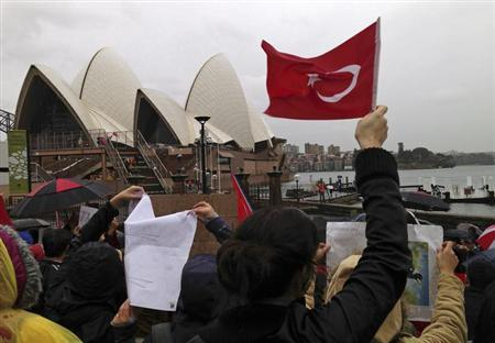 Turkish protesters hold banners and Turkish national flags on the steps of the Sydney Opera House during a protest in Sydney June 2, 2013. REUTERS/Stringer