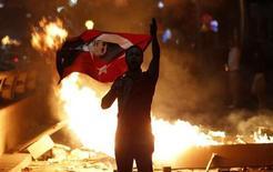 Мужчина держит в руках флаг Турции с портретом Мустафы Кемаля Ататюрка на антиправительственной акции протеста в Анкаре 2 июня 2013 года. Десятки тысяч человек вышли в воскресенье на улицы четырех городов Турции, вступив в схватку с полицейским спецназом, который применил слезоточивый газ на третий день антиправительственных выступлений, самых агрессивных за годы. REUTERS/Umit Bektas