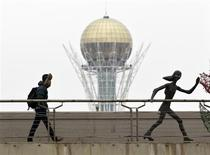 """Человек идет по мосту рядом уличной арт-инсталляцией на фоне 97-метрового монумента Байтерек в Астане 24 марта 2013 года. Генпрокуратура Казахстана назвала """"безосновательным"""" утверждение бежавшего на Запад магната и диссидента Мухтара Аблязова о том, что его жена и дочь депортированы из Италии по указанию президента Нурсултана Назарбаева, но сообщил, что супруге эмигранта отныне запрещено покидать Алма-Ату без разрешения властей. REUTERS/Shamil Zhumatov"""