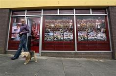 Kevin Maguire, age 62, walks his dog past a vacant shop, with graphics pasted to the outside to make it look like working butchers shop, in the village of Belcoo, Northern Ireland June 3, 2013. The forthcoming G8 summit will be held at a nearby golf resort. Local councils in Northern Ireland have painted fake shop fronts and covered derelict buildings with huge billboards to hide the economic hardship being felt in towns and villages near the golf resort where G8 leaders will meet this month. REUTERS/Cathal McNaughton