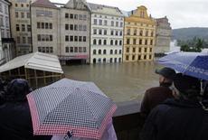 Люди с зонтами смотрят на подтопленные дома на набережной Влтавы в Праге 3 июня 2013 года. Целые кварталы на окраинах Праги во вторник ушли под воду после того, как продолжительные дожди вызвали паводки в Центральной Европе, в результате чего в Чехии, Германии и Австрии уже погибло 11 человек, а более 10.000 были вынуждены покинуть свои дома. REUTERS/David W Cerny