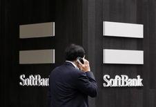 A man using a mobile phone walks past a SoftBank Corp branch in Tokyo May 29, 2013. REUTERS/Toru Hanai