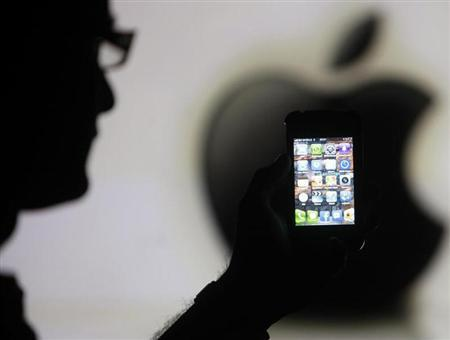 A man is silhouetted against a video screen with an Apple logo as he poses with an Apple iPhone 4 smartphone in this photo illustration taken in the central Bosnian town of Zenica, May 17, 2013. REUTERS/Dado Ruvic