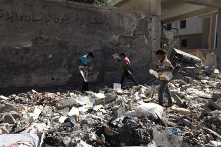 Children walk among rubble in a damaged street as they tear posters in Raqqa province, east Syria, June 4, 2013. REUTERS/Nour Kelze