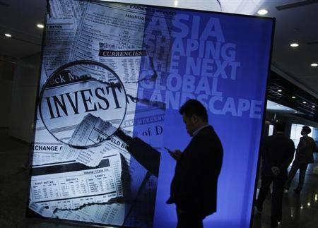 A participant stands in front of a backdrop during the Asian Financial Forum in Hong Kong January 14, 2013. REUTERS/Bobby Yip