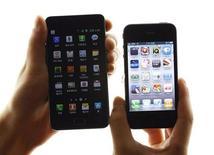 Сотрудник магазина в Сеуле держит девайсы Apple iPhone 4 (справа) и Samsung Galaxy S II, 25 августа 2011 года. Samsung Electronics одержала победу над своим конкурентом Apple Inc в продолжительном споре о патентных правах на мобильные технологии, добившись введения запрета на продажу некоторых моделей iPad и iPhone на американском рынке. REUTERS/Jo Yong-Hak