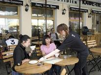 Официантка обслуживает посетителей кафе в центре Москвы 18 июня 2008 года. Темпы роста сектора услуг РФ в мае 2013 года снизились из-за продолжительных праздников и стали минимальными с сентября 2010 года, свидетельствует исследование компании Markit, проведенное для HSBC. REUTERS/Sergei Karpukhin