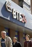 Пешеходы проходят мимо отделения банка ВТБ в Москве 29 апреля 2013 года. Второй по величине госбанк ВТБ хочет увеличить капитал за счет положенной акционерам прибыли, выплачивая часть дивидендов акциями, и Центробанк готов идее содействовать. REUTERS/Sergei Karpukhin