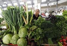Женщина продает овощи на рынке в Санкт-Петербурге 9 июня 2011 года. Рост потребительских цен в России с 28 мая по 3 июня 2013 года составил 0,1 процента, тогда как в предыдущие две недели недельная инфляция держалась на уровне 0,2 процента, сообщил Росстат в среду. REUTERS/Alexander Demianchuk