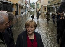German Chancellor Angela Merkel (C) inspects a flooded street near the Elbe river in the east German town of Pirna June 4, 2013. REUTERS/Thomas Peter
