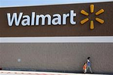 People walk past a Wal-Mart sign in Rogers, Arkansas in this June 4, 2009 file photo. REUTERS/Jessica Rinaldi/Files