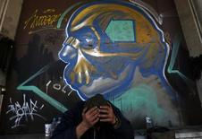 Yannis, a 53-year-old unemployed chef, sits with his head in his hands in front of a graffiti mural in central Athens January 28, 2013. REUTERS/Yannis Behrakis