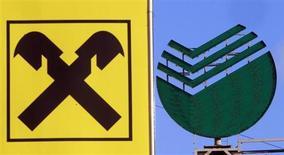 Логотип Raiffeisen рядом с логотипом Сбербанка на улице Москвы 5 декабря 2012 года. Raiffeisen Bank International (RBI) может продать российские активы после ухода Герберта Степича, превратившего компанию в банковскую империю Центральной и Восточной Европы. REUTERS/Sergei Karpukhin