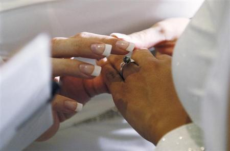 A woman puts a ring on the hand of another woman in a civil union ceremony after Colorado's civil union law went into effect in Denver May 1, 2013. REUTERS/Rick Wilking
