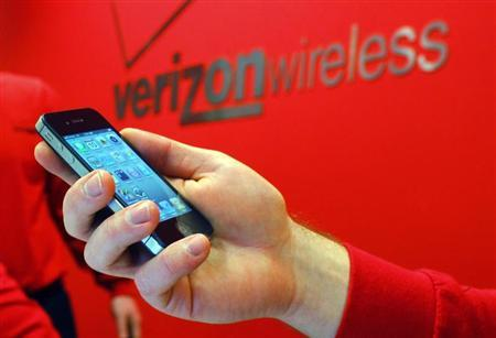 An employee holds out an iPhone for a customer at a Verizon store in Boston, Massachusetts February 10, 2011. REUTERS/Brian Snyder