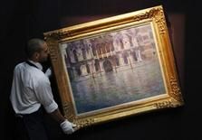 "A Sotheby's employee poses with Claude Monet's artwork ""Le Palais Contarini"" at Sotheby's auction house in London June 7, 2013. REUTERS/Luke MacGregor"
