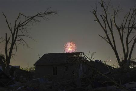 Memorial Day fireworks explode over a house damaged by the May 20 afternoon tornado in Moore, Oklahoma May 26, 2013. REUTERS/Lucas Jackson