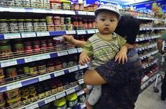 A customer holds a child while shopping at a supermarket in Shenyang, Liaoning province, June 9, 2013. REUTERS/Stringer