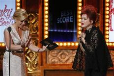 """Singer Cyndi Lauper enters the stage to accept the award for Best Original Score (Music and/or Lyrics) Written for the Theatre for """"Kinky Boots"""" from presenter Jane Krakowski (L) during the American Theatre Wing's annual Tony Awards in New York June 9, 2013. REUTERS/Lucas Jackson"""