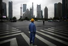 A construction worker looks at Pudong financial district as he wait to cross an avenue in Shanghai in this May 30, 2013 file photo. REUTERS/Carlos Barria/Files