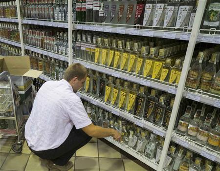 An employee stacks shelves with bottles of vodka from the Crimean Vodka Company (KVK), at a supermarket in Kiev June 6, 2013. REUTERS/Gleb Garanich